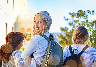 Buy stock photo Rearview shot of university students walking to class on campus
