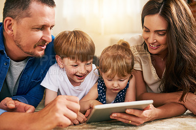 Buy stock photo Shot of an adorable brother and sister using a digital tablet with their parents on the floor at home