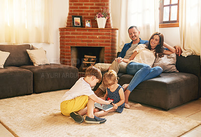 Buy stock photo Shot of an adorable brother and sister using a digital tablet together with their parents relaxing in the background