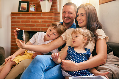 Buy stock photo Shot of a happy young family taking a selfie together on the sofa at home