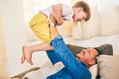 Buy stock photo Shot of a happy little boy having fun with his father at home