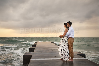 Buy stock photo Full length shot of an affectionate young couple taking in the beach views while standing on a jetty