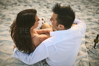 Buy stock photo High angle shot of an affectionate young couple sitting face to face on the beach