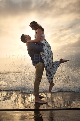 Buy stock photo Full length shot of a handsome young man picking up his girlfriend while standing on the jetty at the beach