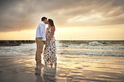 Buy stock photo Full length shot of an affectionate young couple kissing while standing on the beach