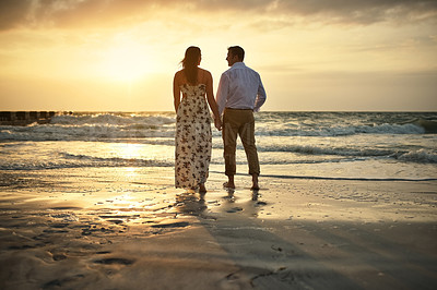 Buy stock photo Rearview shot of an affectionate young couple holding hands while standing face to face on the beach