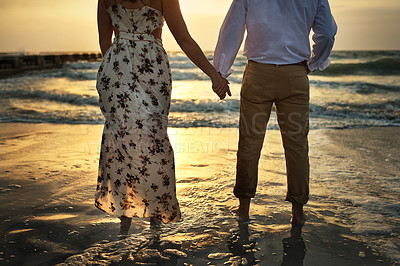 Buy stock photo Rearview shot of an unrecognizable couple holding hands while standing on the beach