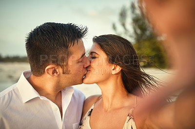 Buy stock photo Cropped shot of an affectionate young couple kissing while taking selfies on the beach