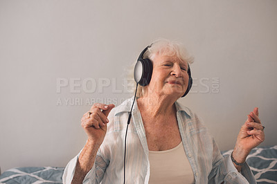 Buy stock photo Shot of a happy senior woman listening to music in an old age home