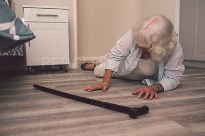 Buy stock photo Shot of a senior woman falling on the floor of a retirement home and reaching for her cane