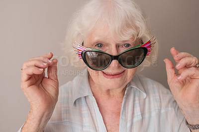 Buy stock photo Portrait of a happy senior woman wearing sunglasses against a gray background