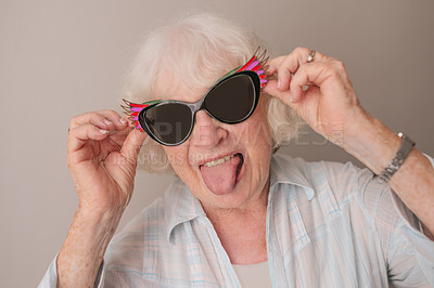 Buy stock photo Portrait of a happy senior woman wearing sunglasses and making faces against a gray background