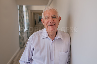 Buy stock photo Shot of a happy senior man leaning against a wall of a retirement home