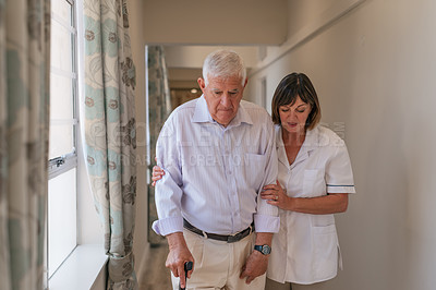 Buy stock photo Shot of a senior man with a cane being cared for by a nurse in an old age home