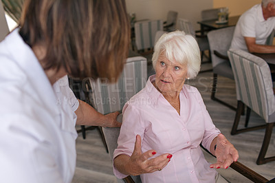 Buy stock photo Shot of a senior woman talking to a nurse in the dining room of a retirement home