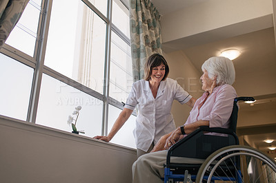 Buy stock photo Shot of a nurse talking with a senior woman in a wheelchair at a retirement home