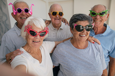 Buy stock photo Shot of a group of senior taking a selfie while wearing funky sunglasses in a retirement home