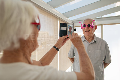 Buy stock photo Shot of a senior couple taking photos while wearing funky sunglasses in a retirement home