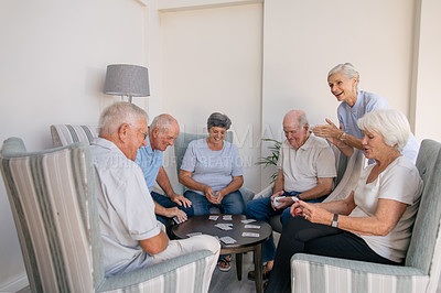 Buy stock photo Shot of a group of senior people playing cards together at a retirement home