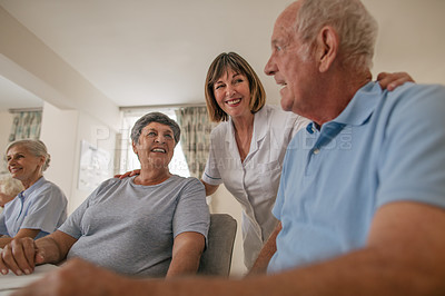 Buy stock photo Shot of a nurse talking to the senior residents in the dining room of a retirement home
