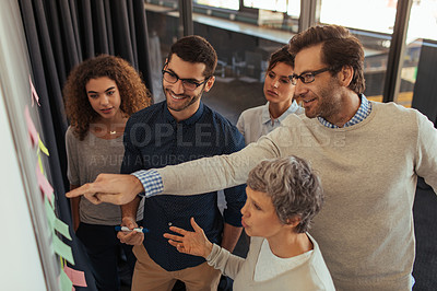 Buy stock photo Shot of a group of businesspeople brainstorming with notes on a whiteboard in an office