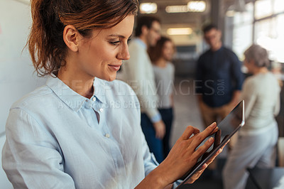 Buy stock photo Shot of a mature businesswoman using a digital tablet in an office with her colleagues in the background