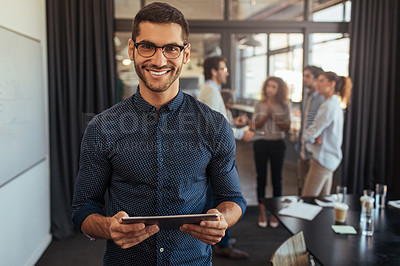 Buy stock photo Portrait of a young businessman using a digital tablet in an office with his colleagues in the background