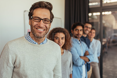 Buy stock photo Portrait of a young businessman standing in an office with his colleagues in a line behind him