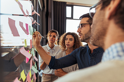 Buy stock photo Shot of a group of businesspeople brainstorming with notes on glass wall in an office