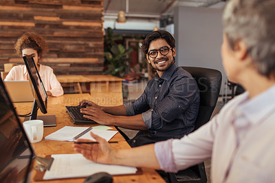 Buy stock photo Shot of two businesspeople having a discussion while working at their desks in an office