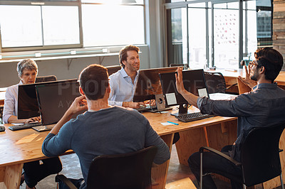 Buy stock photo Shot of businesspeople having a discussion while working at their desks in an office