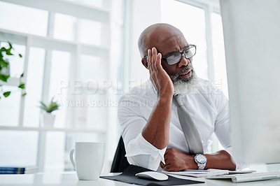 Buy stock photo Cropped shot of a handsome mature businessman looking stressed while working on his computer in the office