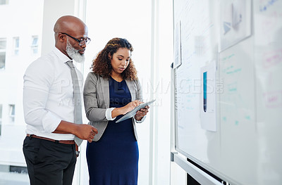 Buy stock photo Cropped shot of two business colleagues using a tablet while working together in their office