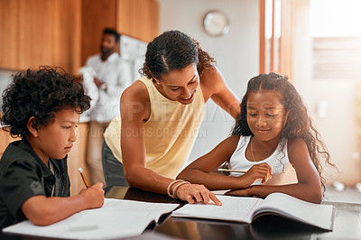 Buy stock photo Shot of a mom helping her children with their homework