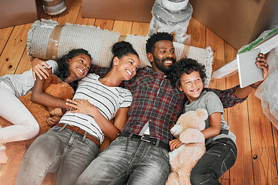 Buy stock photo Shot of a family of four lying together on the floor in their new home