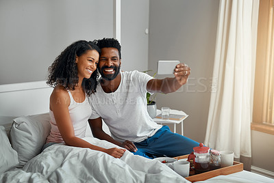 Buy stock photo Cropped shot a young attractive couple taking a selfie while having breakfast in bed at home