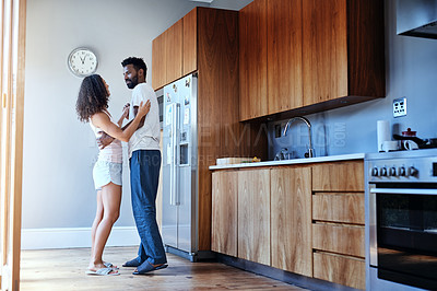 Buy stock photo Full length shot of an affectionate young couple dancing in their kitchen at home