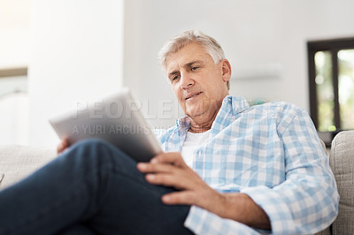 Buy stock photo Cropped shot of a handsome mature man using a tablet while sitting on the sofa at home