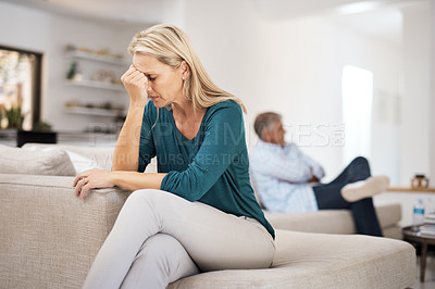 Buy stock photo Cropped shot of a mature woman looking despondent after having a fight with her husband at home