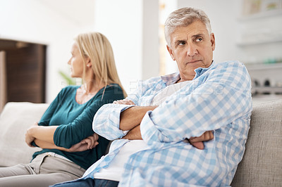 Buy stock photo Cropped shot of a mature couple looking despondent after having a fight with one another at home