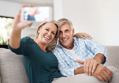 Buy stock photo Cropped shot of an affectionate mature couple taking selfies together while sitting on the sofa at home