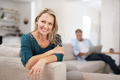Buy stock photo Portrait of an attractive mature woman relaxing at home with her husband in the background