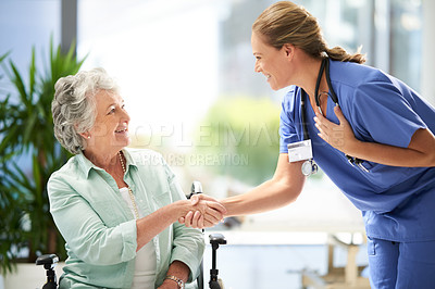 Buy stock photo Cropped shot of an attractive female nurse shaking hands with her wheelchair-bound senior patient in the hospital