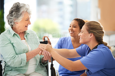 Buy stock photo Cropped shot of two attractive female nurses talking with their wheelchair-bound senior patient in the hospital