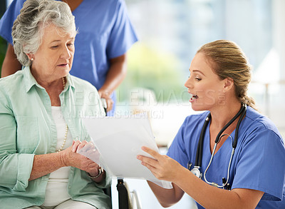 Buy stock photo Cropped shot of an attractive female nurse discussing treatments with her wheelchair-bound senior patient in the hospital