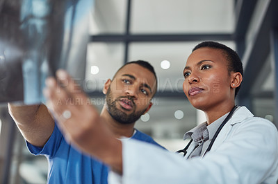 Buy stock photo Shot of two medical practitioners analyzing an x-ray in a hospital
