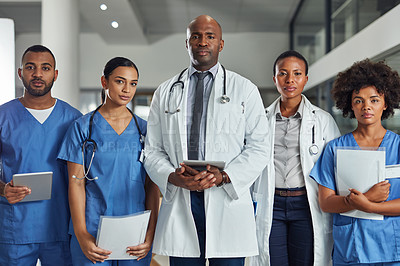 Buy stock photo Portrait of a group of medical practitioners standing together in a hospital