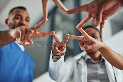 Buy stock photo Closeup shot of a group of medical practitioners joining their fingers together in a hospital
