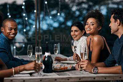 Buy stock photo Shot of a group of friends having dinner outside at a restaurant