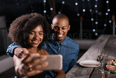 Buy stock photo Cropped shot of a couple taking a selfie while out on a dinner date
